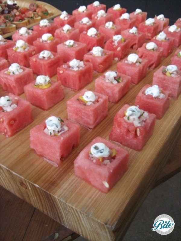 Refreshing watermelon bite with gazpacho, served on wooden display.