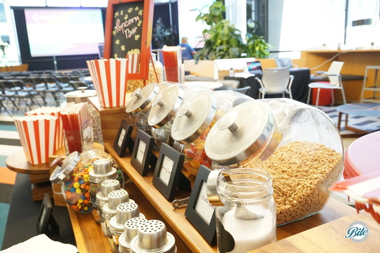 Popcorn and Candy Bar setup behind stage and chairs. Great for a networking or panel event!