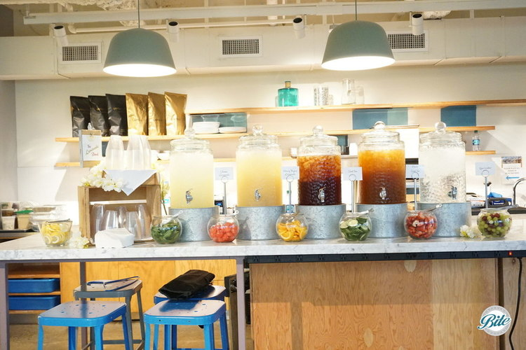 A drink station in the kitchen behind the main event. Ice tea, lemonade, infused spa water, and more to keep people lively during and after the presentation. Presented in glass jars and accompanied with fruit and herbs.