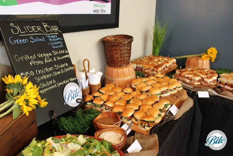 Slider bar station with: Grilled veggie pesto sliders, BBQ chicken sliders, and green salad on a rustic display with sunflowers and custom chalkboard signage