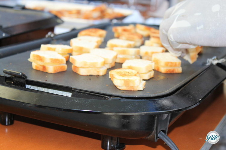 mini grilled cheese sandwiches cooking on the griddle