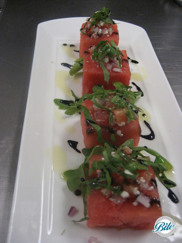 Seasonal summer Watermelon cube bite with balsamic reduction and fresh herbs