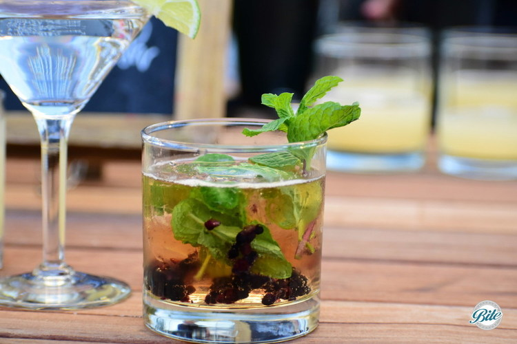 Signature cocktail with blackberries, mint, bourbon, club soda. On wooden table