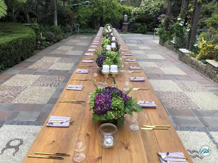 Long wooden table set up with candles and flowers for a plated meal following a wedding reception