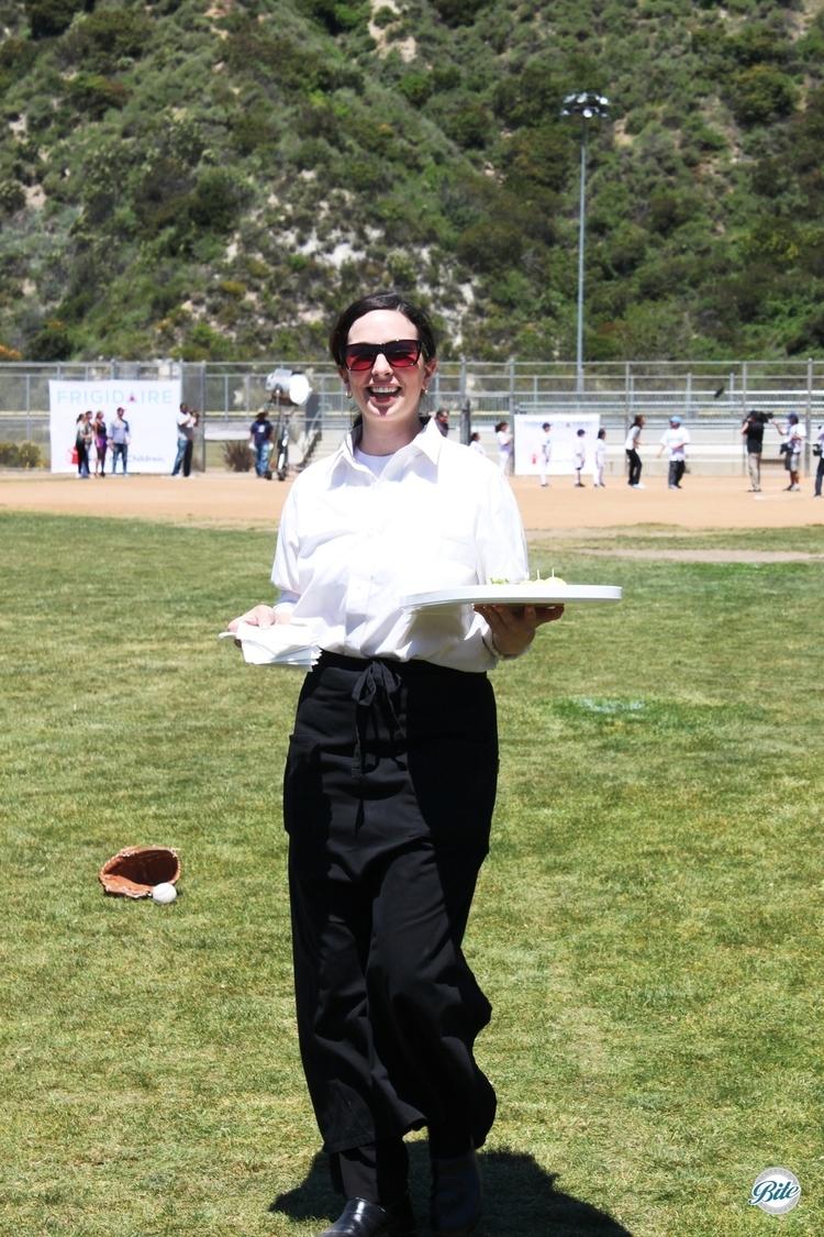 Server walking across baseball field to provide themed refreshments