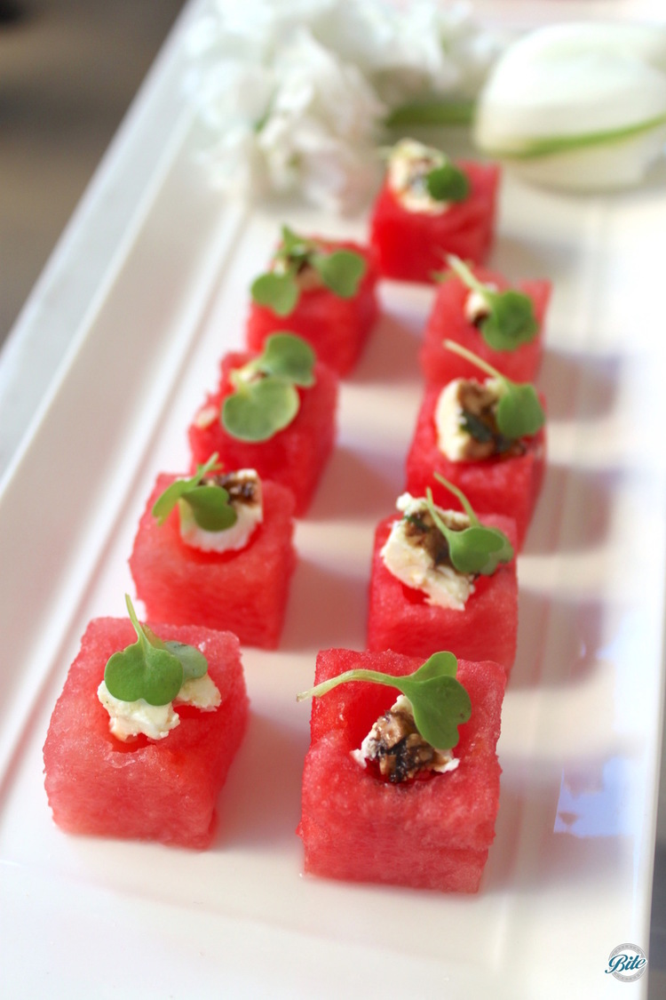 Watermelon salad cube with feta, balsamic reduction, and micro greens. Served on white tray