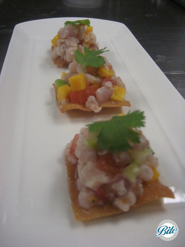 Seasonal ceviche bite served on wonton chip with tropical salsa and cilantro garnish served tray passed