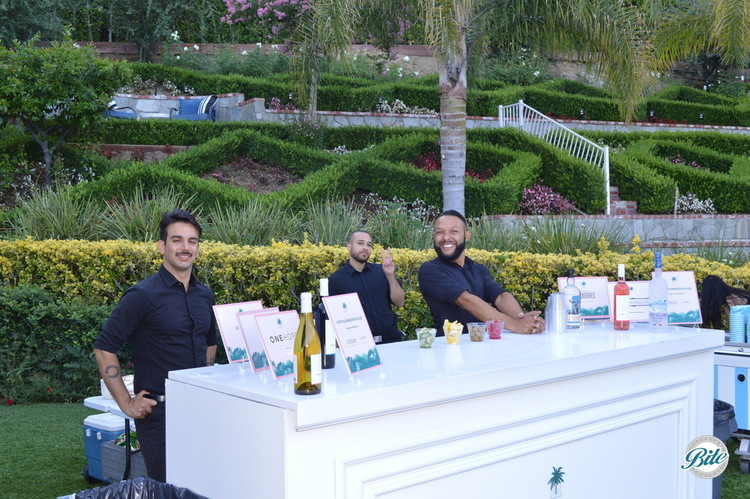 Bartenders pouring drinks at an outdoor bar in the gardens