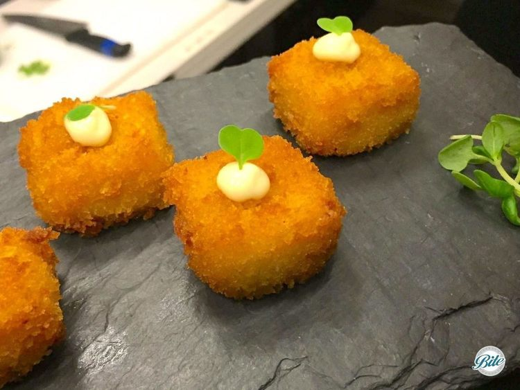 Tray passed mac n cheese bites. Topped with aioli and microgreen