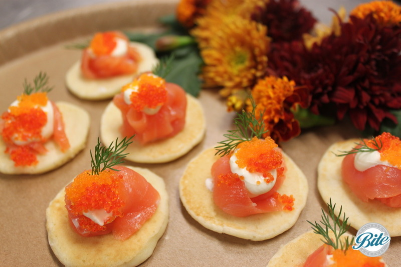 Salmon blini with creme fraiche and caviar with herb and fresh flower garnish