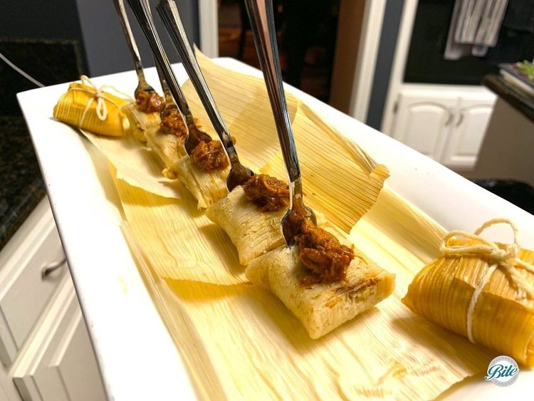 Mini tamales with pork. Passed on white platter with traditional corn husk wrapping