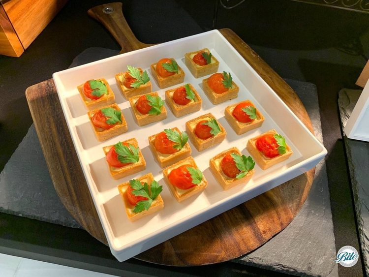 Array of tomato and herb tarts displayed in rows in a white bowl