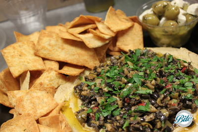 Hummus with olive tapenade, pita chips, and marinated olives with cheese on the side