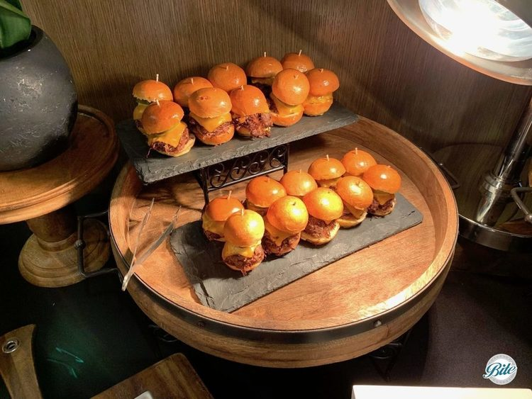 Short Rib Sliders on two levels displayed on slate trays on wooden table