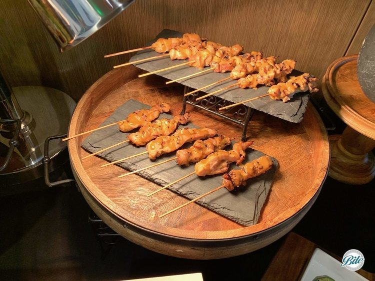 Chicken satay skewers displayed on two level slate trays