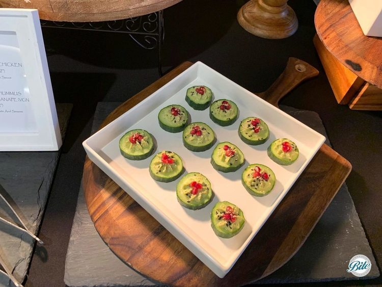 Cucumber canape with pomegranate and sesame. Displayed on white tray