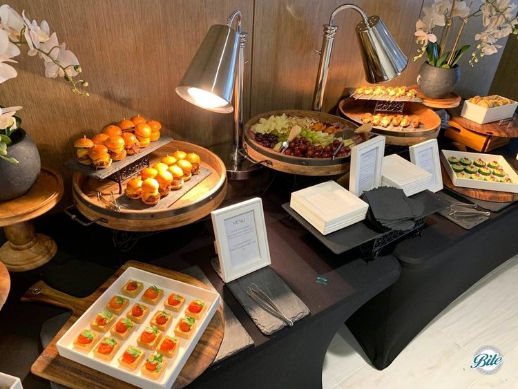 Bites display laid out for corporate reception. Sliders, herb tarts, satay, canapes, and antipasto