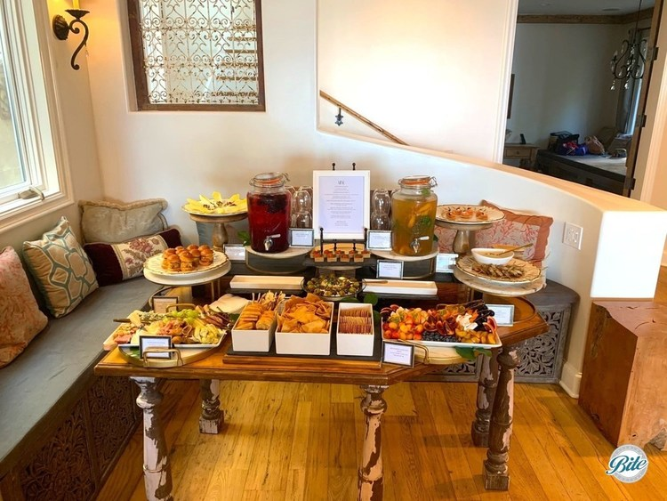 Welcome appetizers laid out on an entry table. Antipasto, meze, seasonal fruits, herb tart, endive canapes, blini, sliders. With lemonade and iced tea