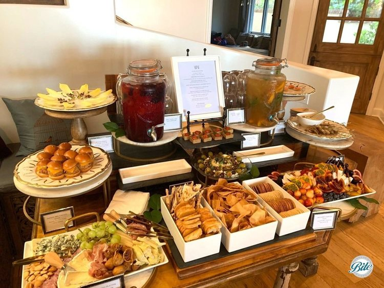 Welcome appetizers laid out on an entry table. Antipasto, meze, seasonal fruits, herb tart, shrimp, endive canapes, blini, sliders, and crackers. With lemonade and iced tea