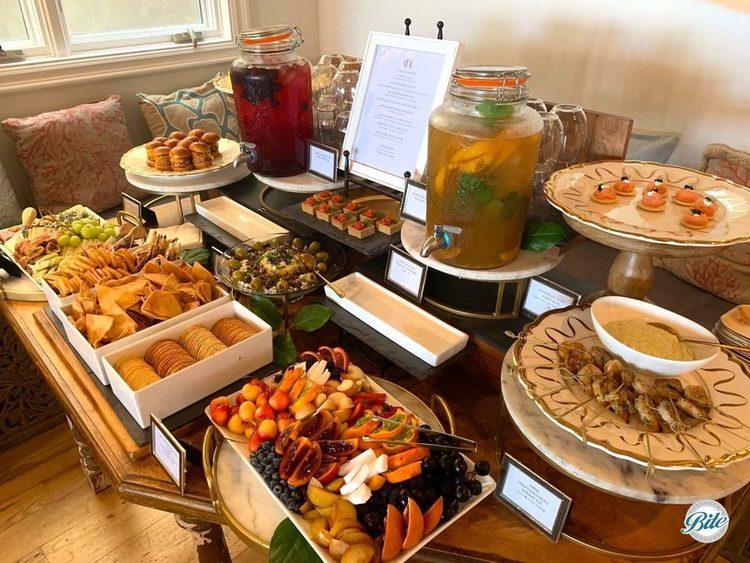 Bites display including fruit, blini, shrimp, meze, crackers, herb tarts. antipasto, sliders, and fruit infused beverages