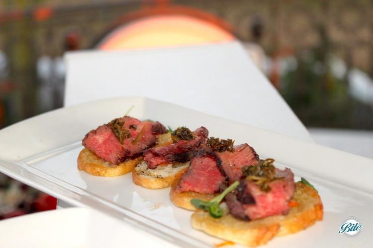 Flank steak crostini on a white tray.