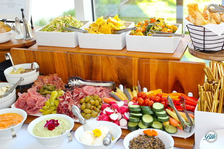 Display with vegetables, spreads, charcuterie, artisan breads, feta, burrata, and salads