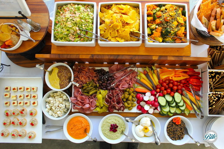 Overhead view of display with multiple salads, crudite, charcuterie, bread, spreads, and bites