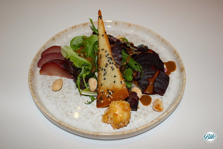 Starter coarse of a winter salad with beets, pears, goat cheese, marcona almonds, balsamic dressing, topped with a sesame touille