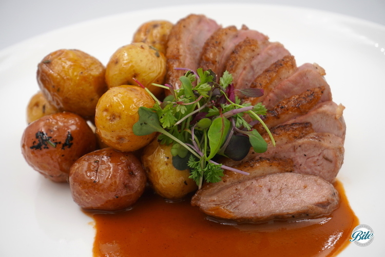 Seared duck breast with a honey lemon glaze and ginger lemongrass jus. Served plated with oven roast potatoes.