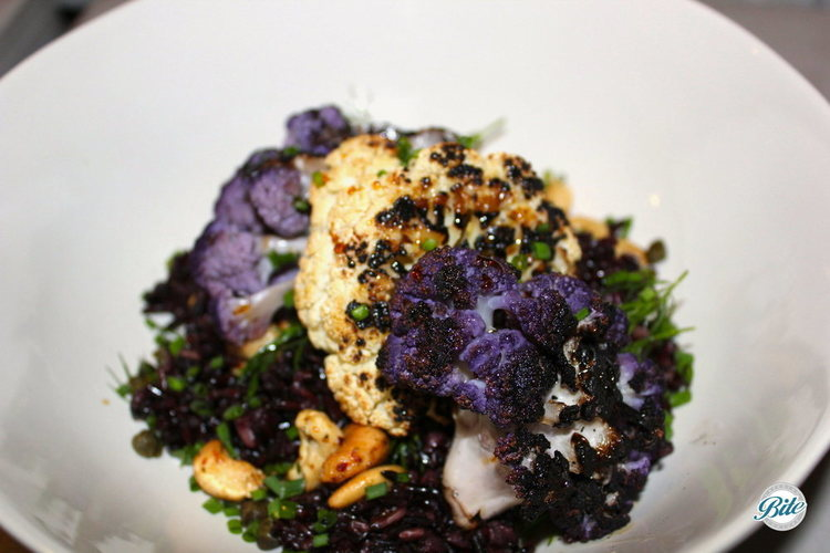 purple and white cauliflower marinated in harissa and grilled. On a bed of greens, with sweet carrot relish and toasted nuts.