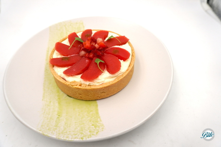 Tart with strawberry topped with creme fraiche, whipped cream, basil oil. Plated.