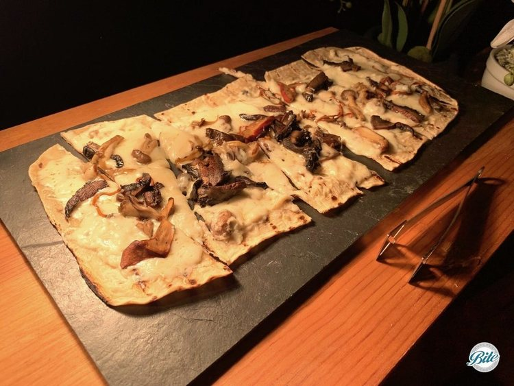 Flatbread with truffle bechamel sauce, assorted wild mushrooms, and fontina cheese.