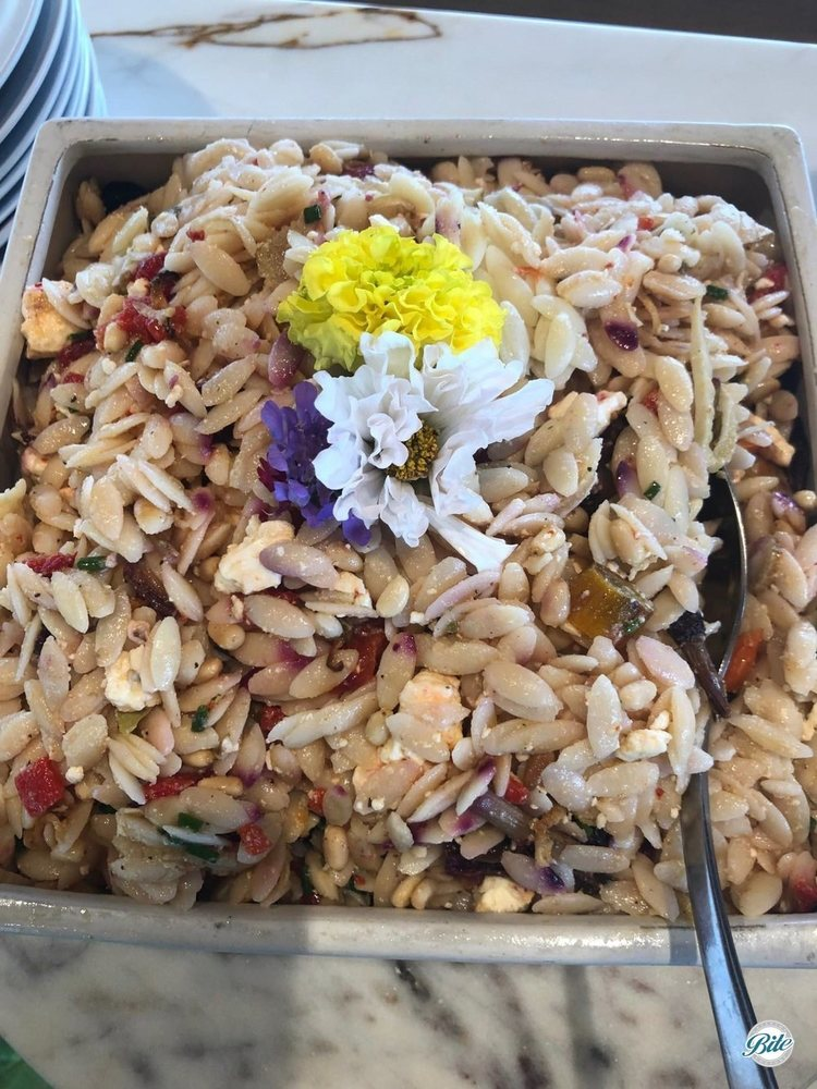 Orzo salad in bowl. With roasted vegetables, lemon vinaigrette, pine nuts, feta and basil. Garnished with flowers.