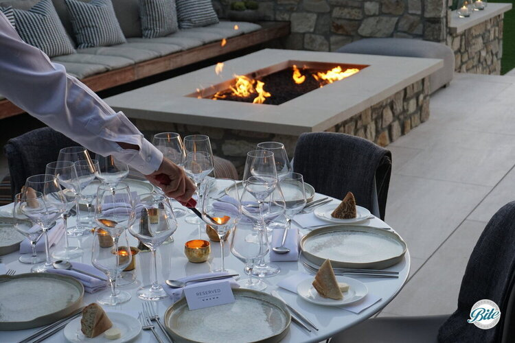 Server lighting candles for an evening dinner service outdoors