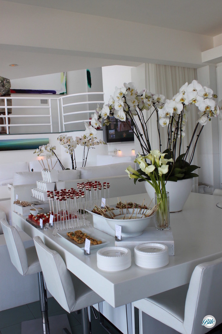 All white, modern food display with vertical caprese skewers, watermelon cubes with balsamic and basil, arranged with orchids for presentation