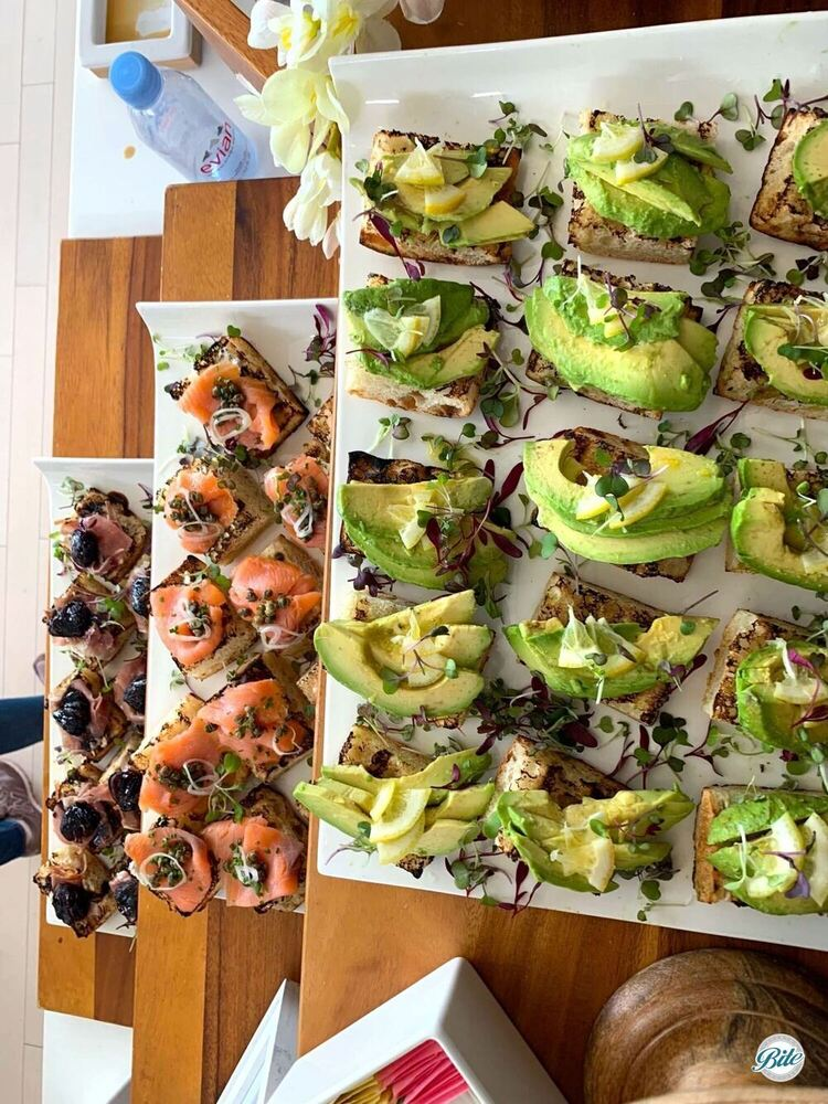 View from above of a tartine section of a breakfast display. Fig and prosciutto, smoked salmon and caper, and avocado.