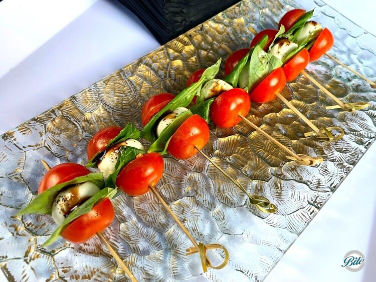 Caprese skewers on metallic passing tray. Tomato, mozzarella, basil, balsamic.