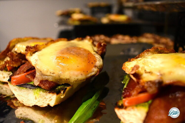 Closeup of hearty egg tartine with egg and bacon.