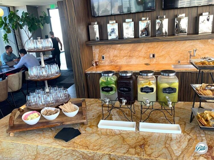 Drink display setup with water, iced tea, lemonade, and pear lemonade at the end of the bar.