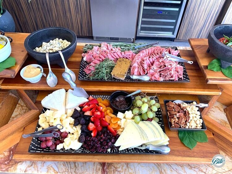 Cheese and charcuterie platters laid out on grazing table. Variety of cheese with fruit and nuts combined with a variety of meats, pate, pickled accompaniments, mixed olives, and more!