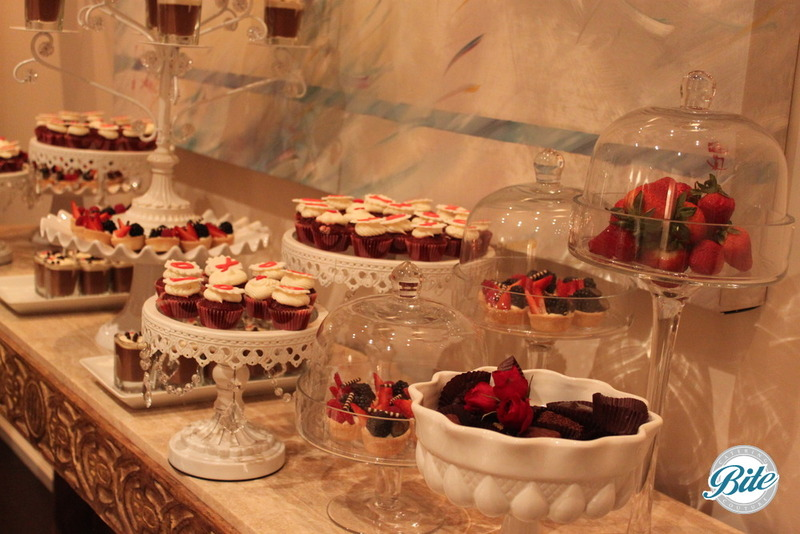 Valentine dessert display XO cupcakes, handmade chocolates, fruit tarts and pot de crème on porcelain and glass dishes