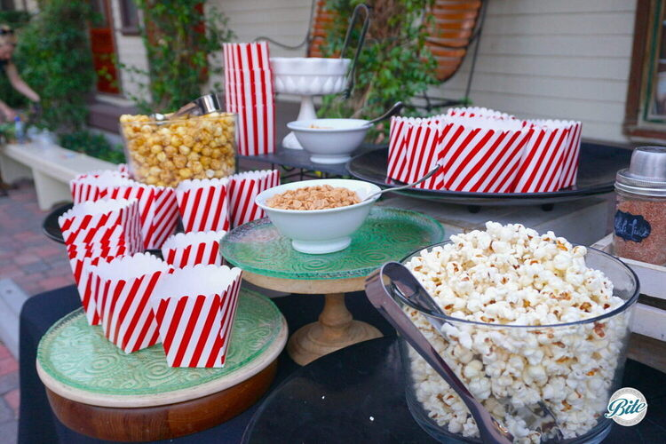 Popcorn laid out for popcorn bar with red and white cups. Classic and caramel flavors. Chili lime flavor in shaker.