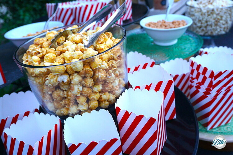 Closeup of caramel popcorn in clear bowl with tongs. Red and white striped popcorn cups for service.
