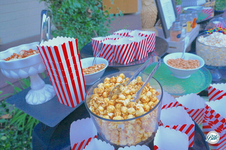 Popcorn bar with caramel popcorn, nuts, and popcorn boxes. Flavors in shakers in the background.