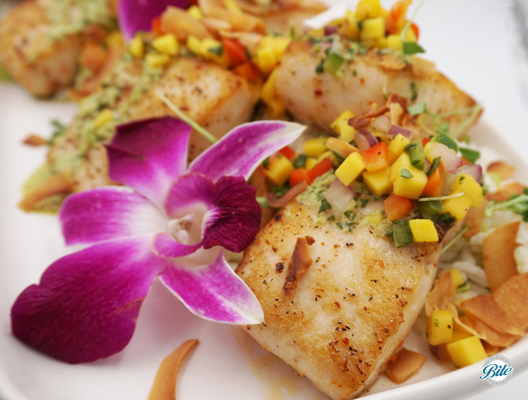 Pan seared mahi mahi with coconut salsa verde and mango coconut salad. Garnished with flowers.