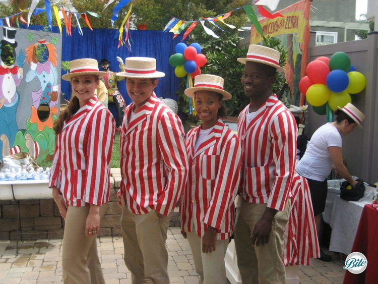 Bite servers at in striped coats, hats and khakis for outdoor carnival themed event