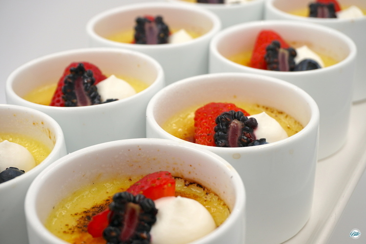 Mini creme brulee. Served in white cups with cream and seasonal berries.