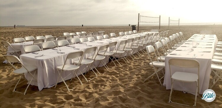 Tables and chairs set up on the beach in front of a volleyball net.