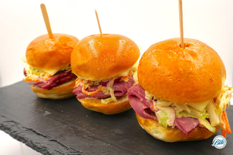 Corned beef sliders for St. Patrick's Day! With cabbage slaw, swiss cheese, and Guinness garlic-mustard aioli