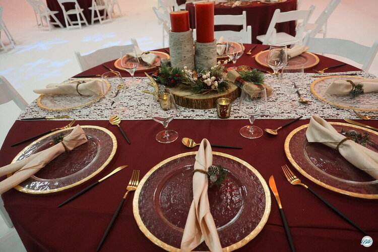 Table set for event with gold utensils. Centerpiece with tall red candles and pine with red berries on wood centerpiece.